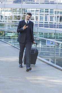 Businessman with cell phone walking with suitcase on bridge - TCF05229