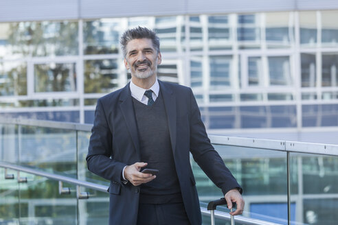 Portrait of smiling businessman outdoors with cell phone - TCF05232