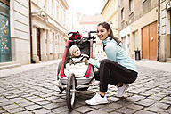 Mother in sportswear with child in stroller in the city - HAPF01205