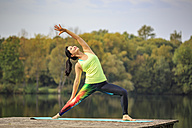 Woman practicing yoga on jetty at a lake - VTF00576