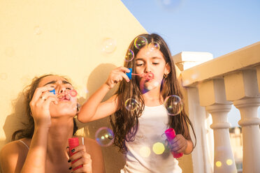 Teenage girl and her little sister blowing soap bubbles on balcony - SIPF01179