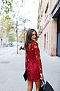 Beautiful young woman wearing red dress carrying shopping bags - VABF00922