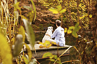 Man with dog on a jetty at a pond in autumn - MFRF00836