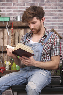 Young gardener taking a break and reading an old botanical book - RTBF00584