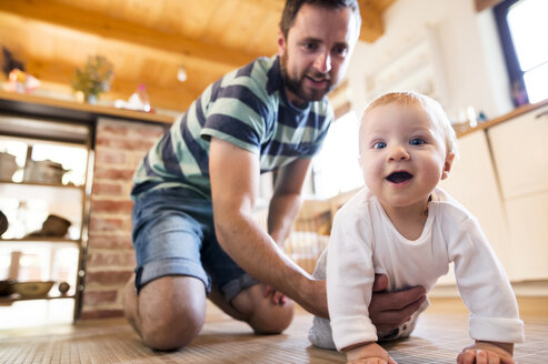 Father supporting crawling baby at home - HAPF01213