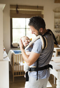 Happy father with baby in baby carrier at home - HAPF01228