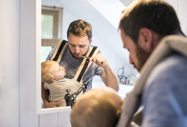 Father with baby in baby carrier brushing his teeth - HAPF01231