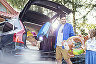 Father and daughters packing car boot for family vacation - WEST22299
