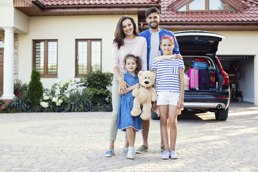 Happy family standing in front of car packed for vacation - WEST22308
