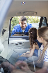 Father standing at car window, talking to his daughters sitting in back seat - WEST22314