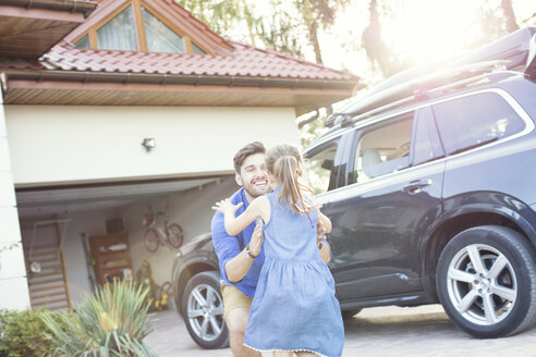 Father and daughter embracing in front of their car - WEST22326