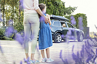 Mother and daughter watching car driving off with second daughter - WEST22329