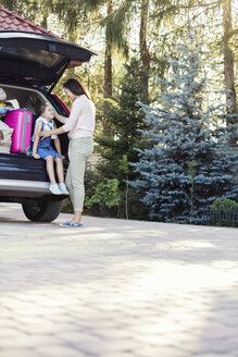 Mother and daughter packing car for family vacation - WEST22335