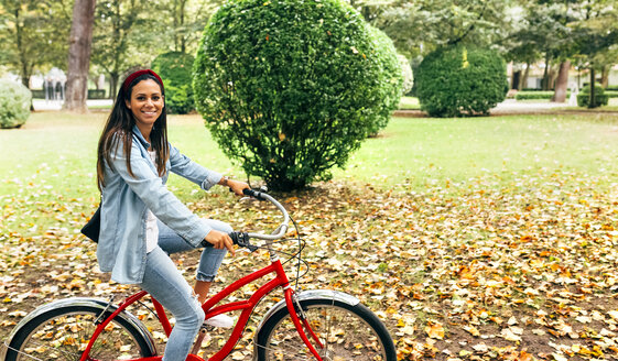 Smiling young woman riding a bike in a park - MGOF02696