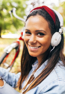 Portrait of smiling young woman listening to music in a park - MGOF02708