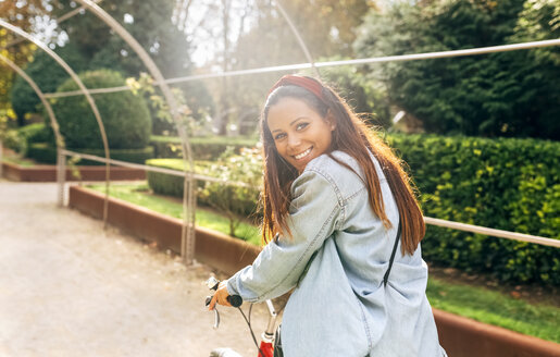 Smiling young woman riding a bike in a park - MGOF02711