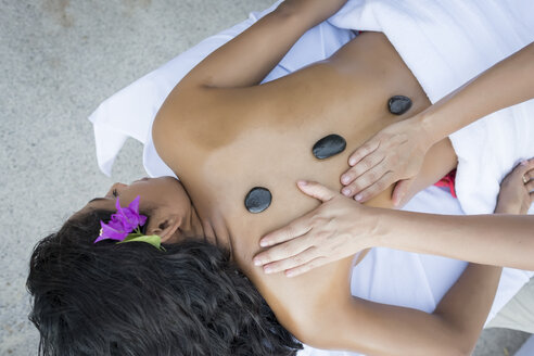 Young woman receiving a massage with heated stones on her back - ABAF02104