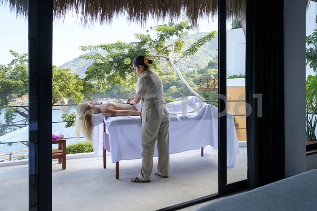 Young woman receiving a massage on the balcony of her suite in a luxury vacation retreat - ABAF02107