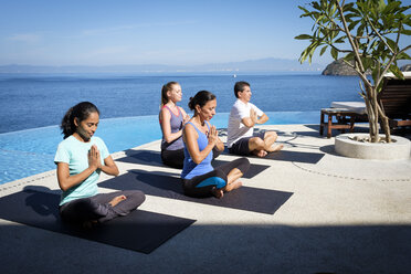 Yoga group exercising at ocean front resort - ABAF02110