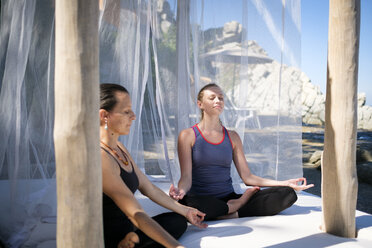 Two women practicing yoga meditation in a cabana - ABAF02119
