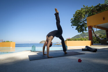 Woman practicing yoga at ocean front resort - ABAF02122