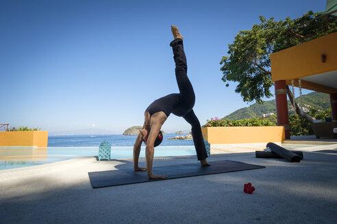 Woman practicing yoga at ocean front resort - ABAF02122