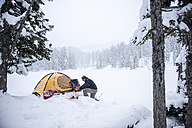 Senior man camping in snow-covered landscape - HHF05484