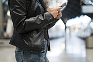 Woman using cell phone at train station - KKAF00185