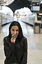 Happy young woman with cell phone at train station - KKAF00188