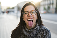 Portrait of happy young woman with glasses sticking her tongue out - KKAF00197