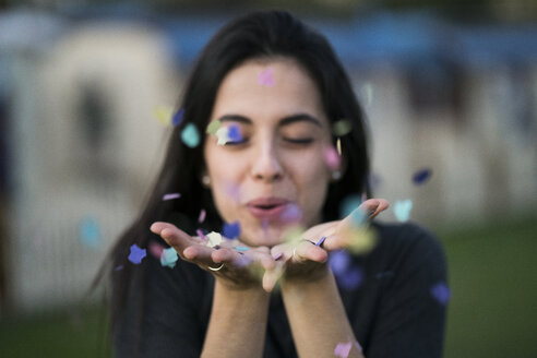 Happy young woman blowing confetti outdoors - KKAF00206