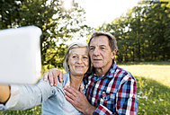 Senior couple taking selfie with cell phone in nature - HAPF01247