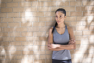 Portrait of confident female athlete leaning against brick wall - GIOF01720