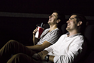 Two men watching a movie in a cinema - ABZF01626
