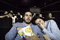 Scared couple watching a movie in a cinema - ABZF01638