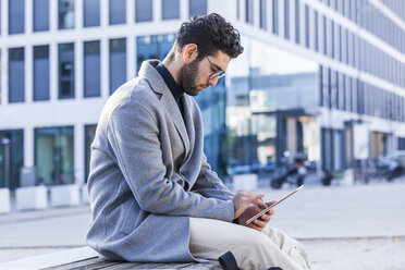 Young man sitting on bench using mini tablet - TCF05247