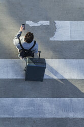Businessman with baggage crossing the street while looking at cell phone, top view - TCF05253