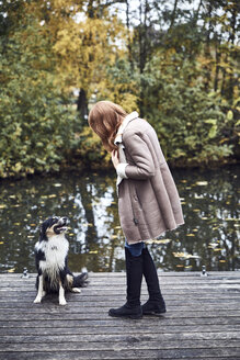 Woman with her dog on jetty in autumn - SRYF00142