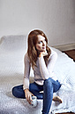 Portrait of redheaded woman sitting on bed with cup - SRYF00145