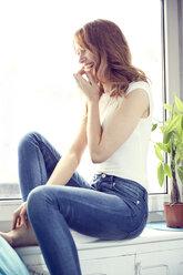 Laughing redheaded woman sitting on window sill - SRYF00151