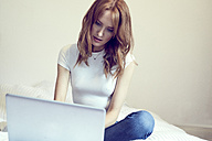 Redheaded woman sitting on bed using laptop - SRYF00160
