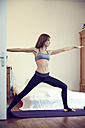 Redheaded woman doing yoga exercise at home - SRYF00172