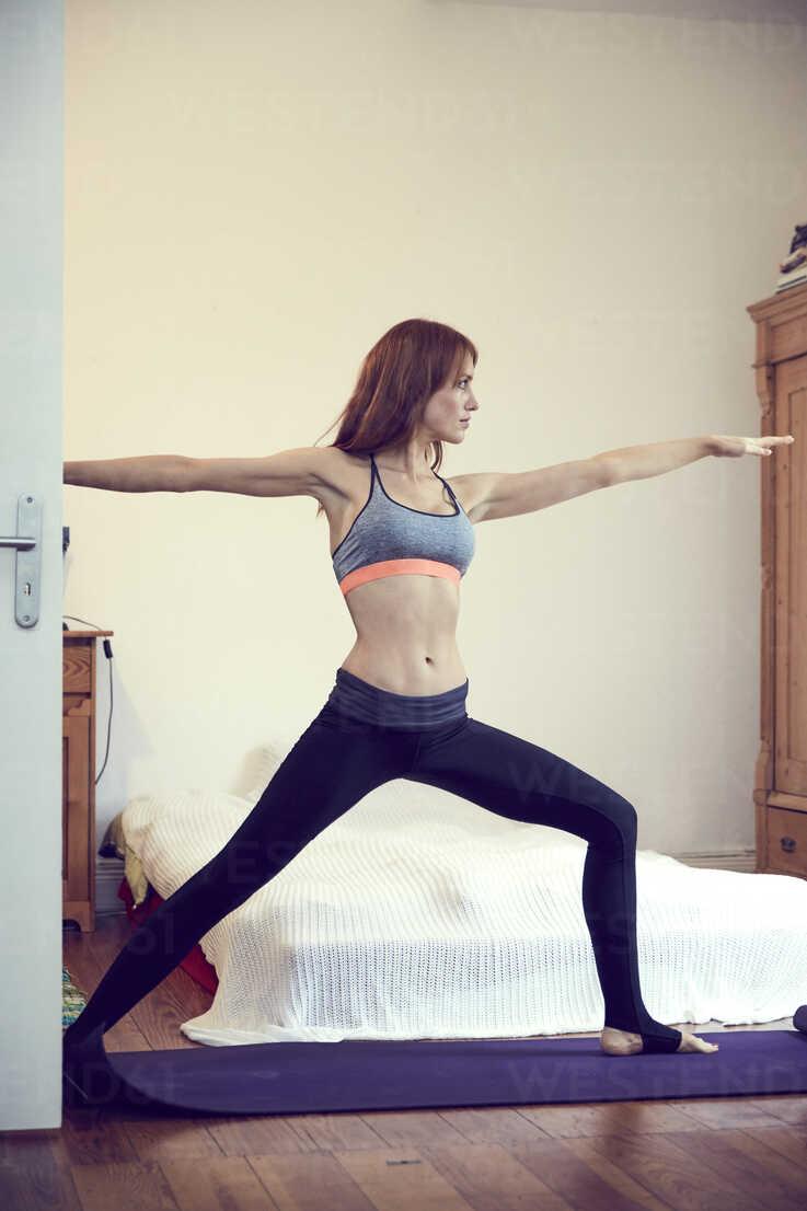 Redheaded woman doing yoga exercise at home - SRYF00172 - Martina Ferrari/Westend61