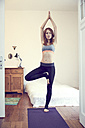 Redheaded woman holding a Vrksasana yoga pose at home - SRYF00175