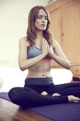 Redheaded woman doing yoga exercise at home - SRYF00181