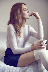 Pensive redheaded woman with cup sitting on bed - SRYF00184