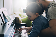 Child and his father playing piano - JPSF00029