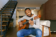 Young man at home playing guitar - VABF00956