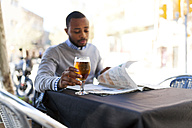 Young man reading newspaper and drinking a beer at street cafe - VABF00962
