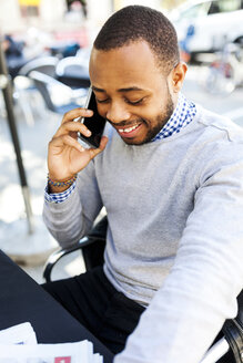 Smiling young man on cell phone at street cafe - VABF00965